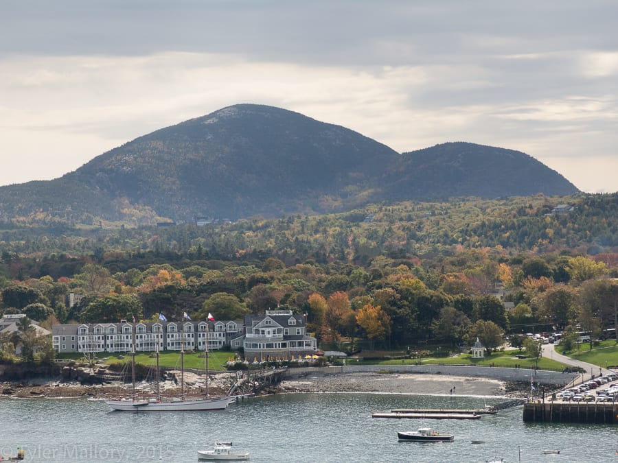 Cadillac Mountain and Acadia National park, ablaze in fall colors, with Bar Harbor in front.
